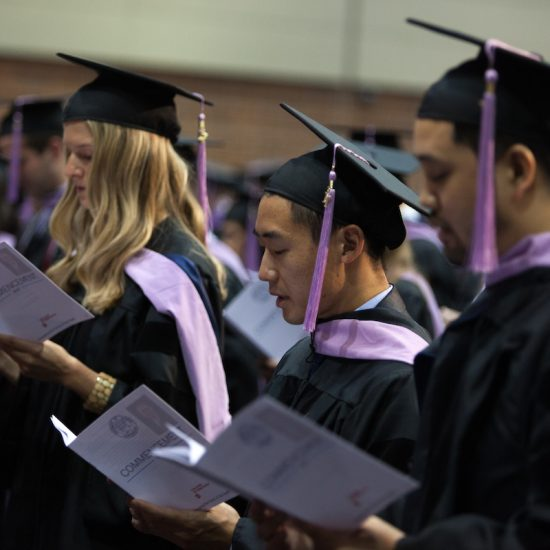 Students in cap and gown reading graduation programs