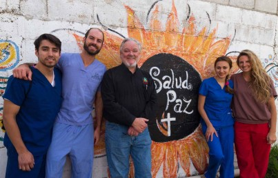 Group of dentist standing against a wall painted with the sun
