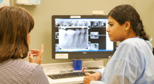 dentist talking to patient in front of computer screen