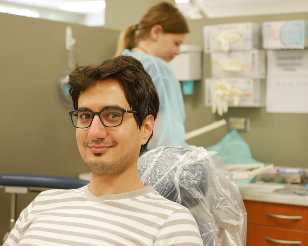 patient smiling at camera with dentist in background