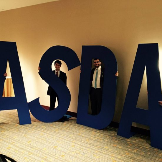 Students standing with large letters A S D A