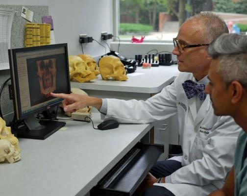 Surgeon pointing at computer screen
