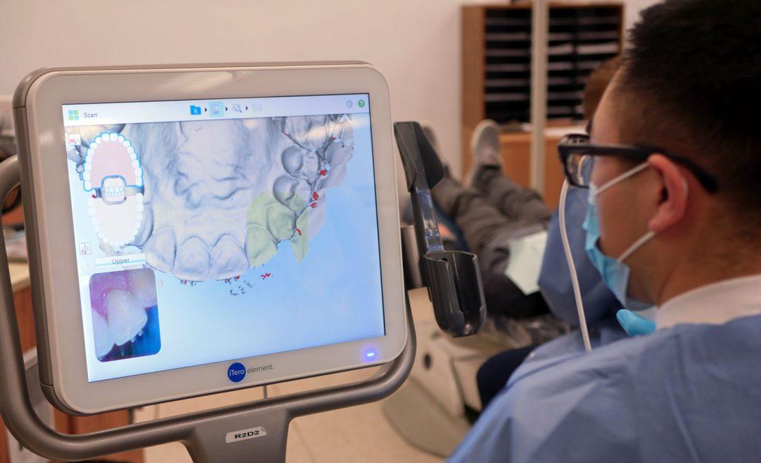 dentist looking at teeth on computer screen