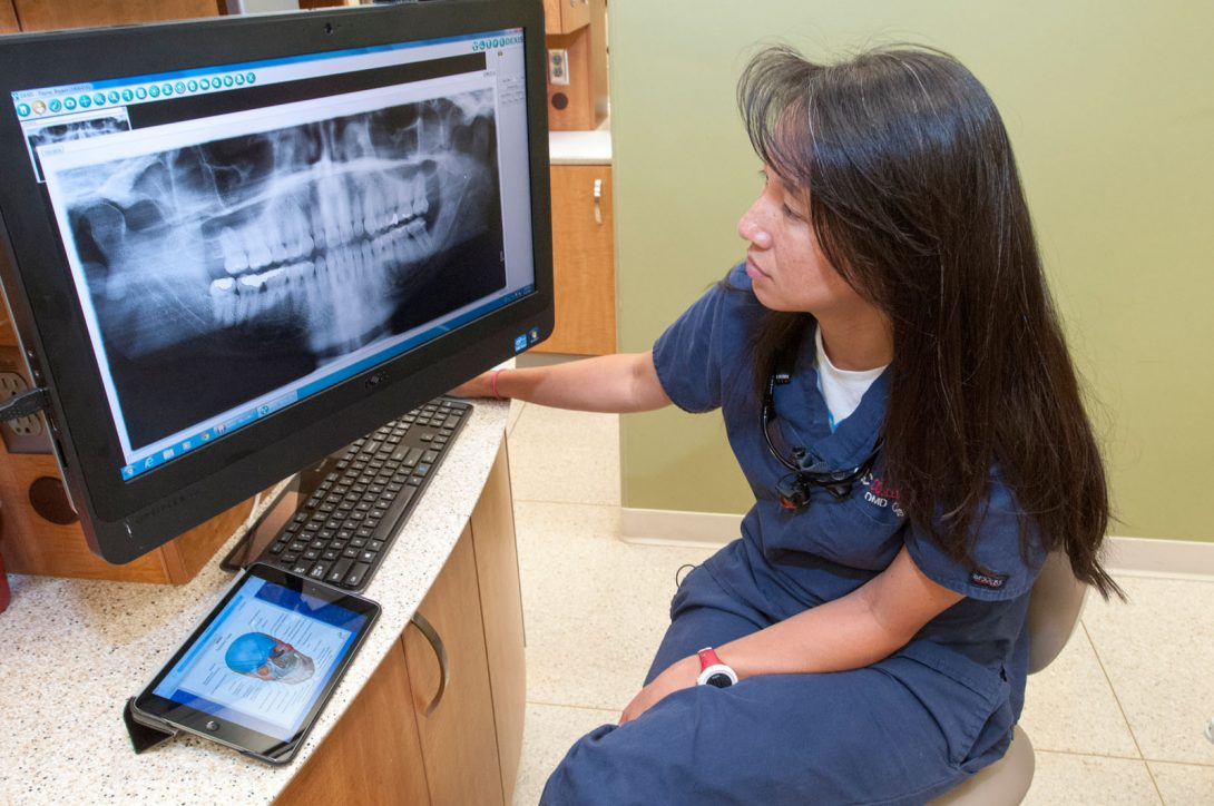 dentist looking at x-rays of teeth on computer screen