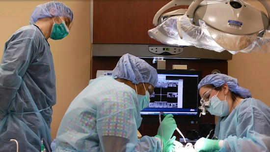three dentists working on patient